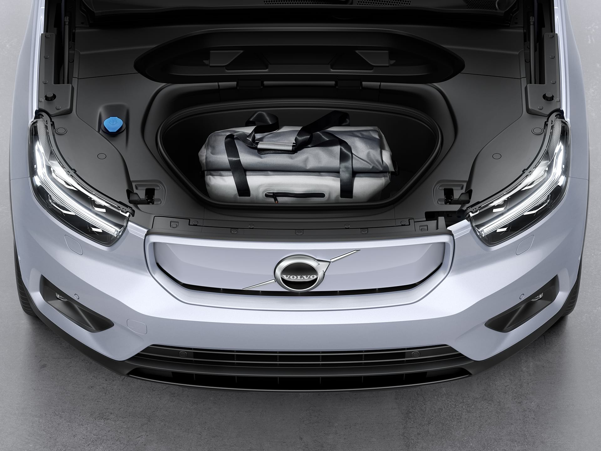 The front compartment of the Volvo XC40 Recharge packed with a sports bag.