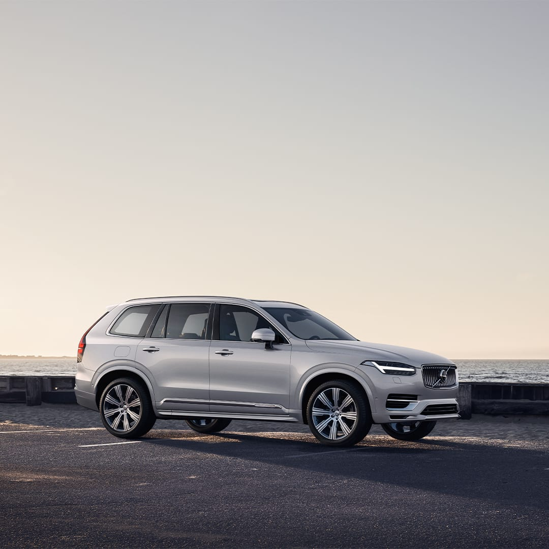 A Volvo XC90 Recharge parked along a road by the sea.