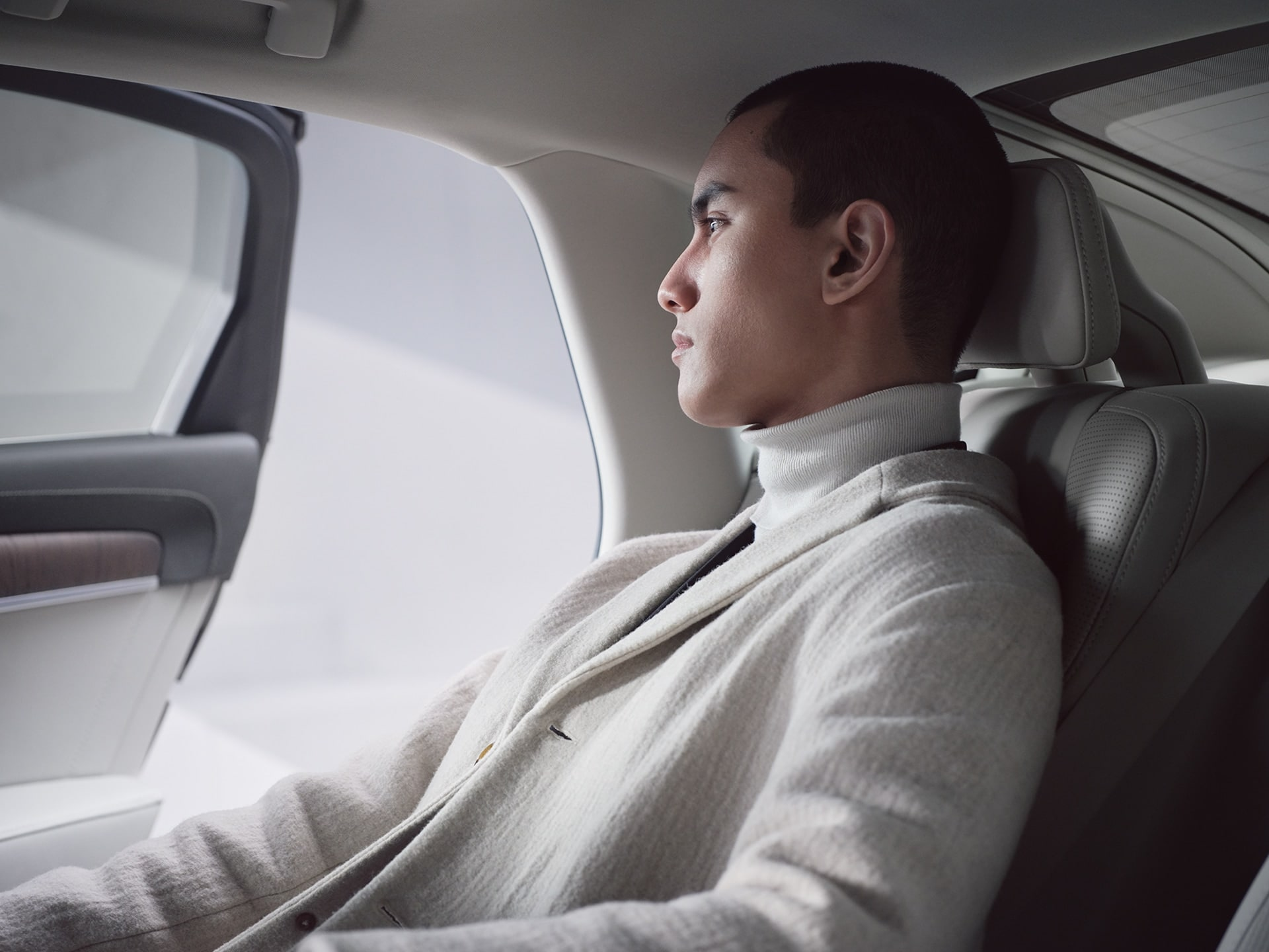 A man sits in the back seat of a Volvo S90 Recharge, looking out, the door is open