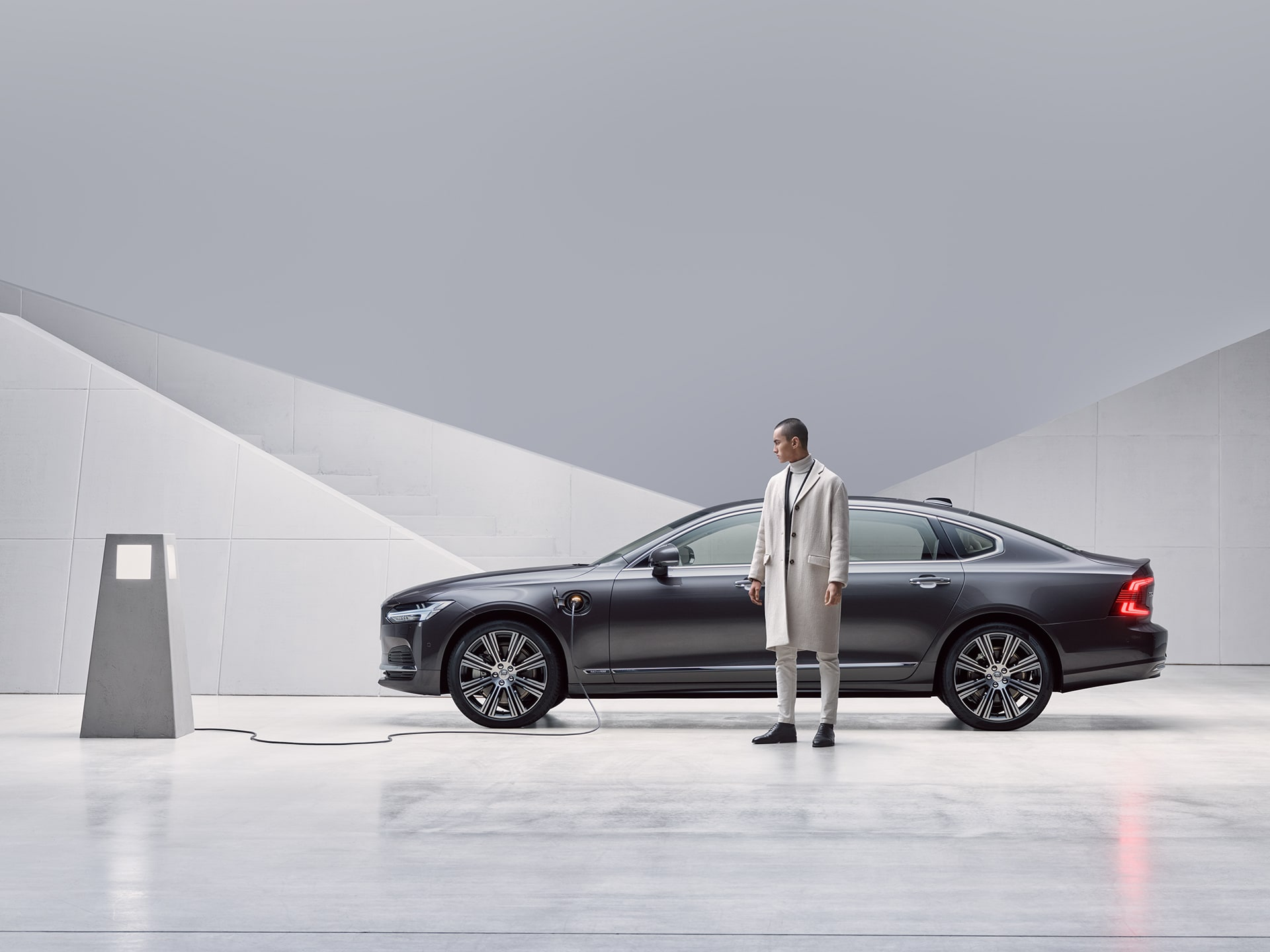 A man is standing in front of his grey Volvo S90 Recharge plug-in hybrid sedan, being charged.