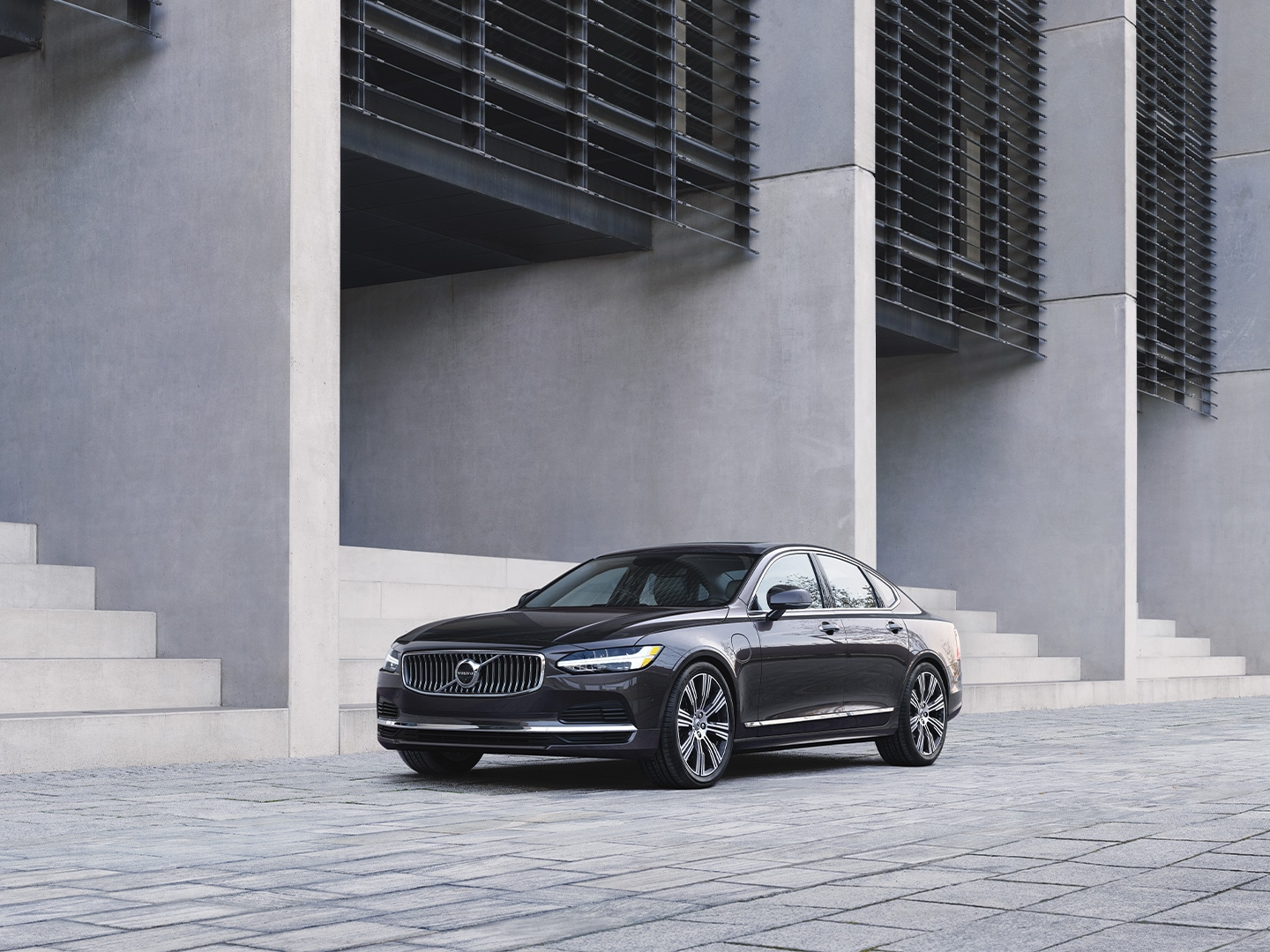 A dark grey Volvo S90 Recharge pure electric parked outside a building