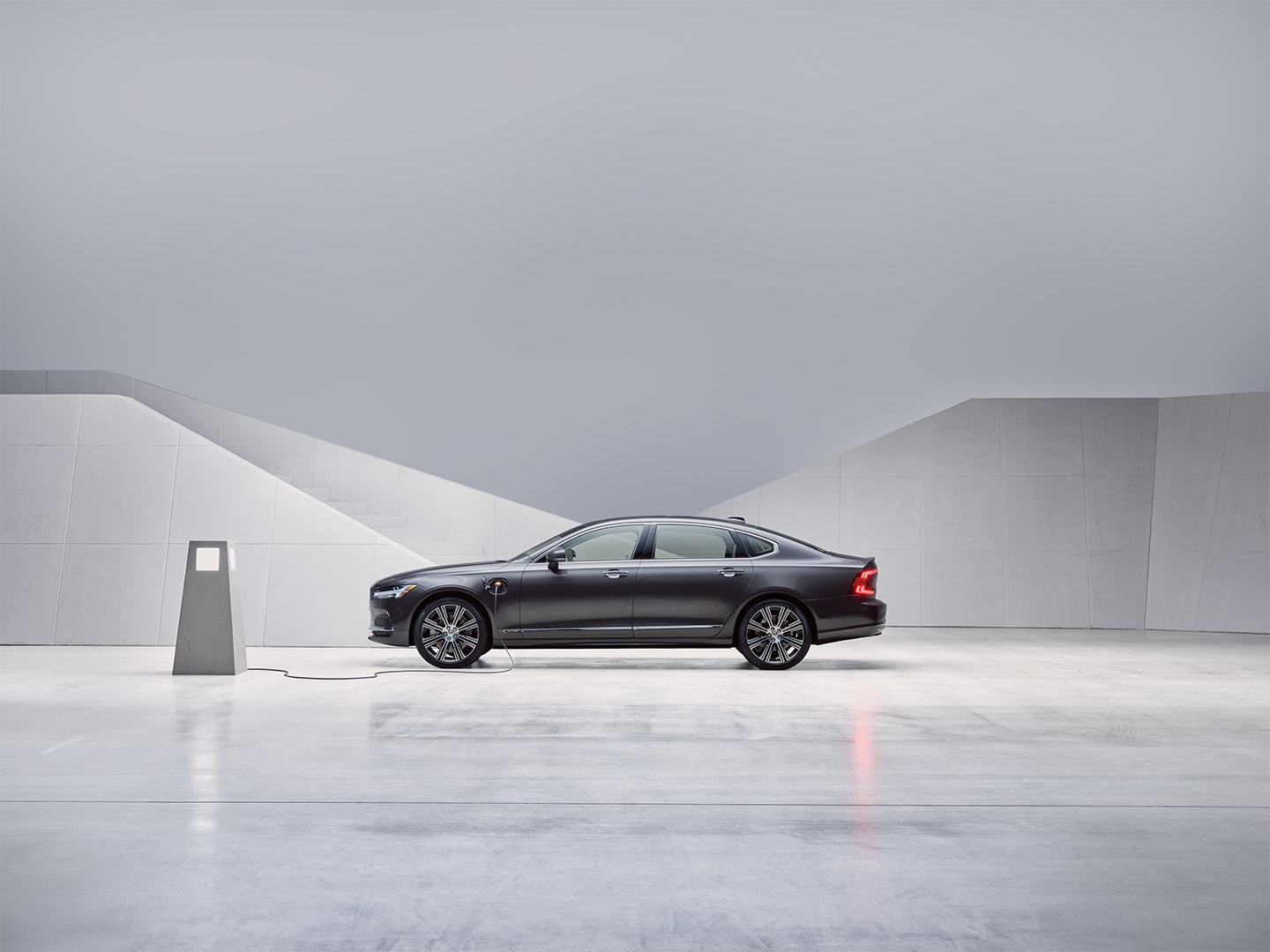 A pebble grey Volvo S90 plugin hybrid sedan standing still and being charged