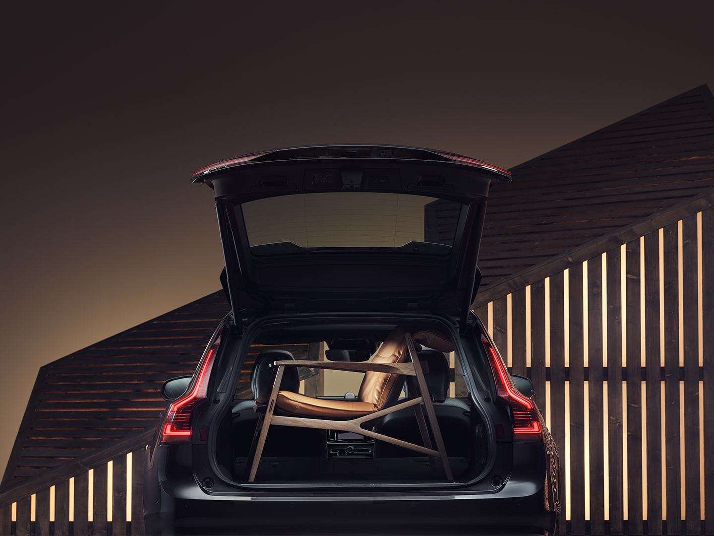 The boot space of a Volvo Wagon is filled up by a brown elegant armchair