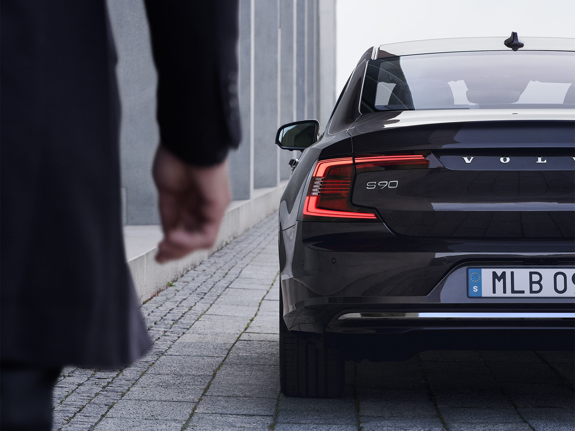 A man walks towards a black Volvo S90