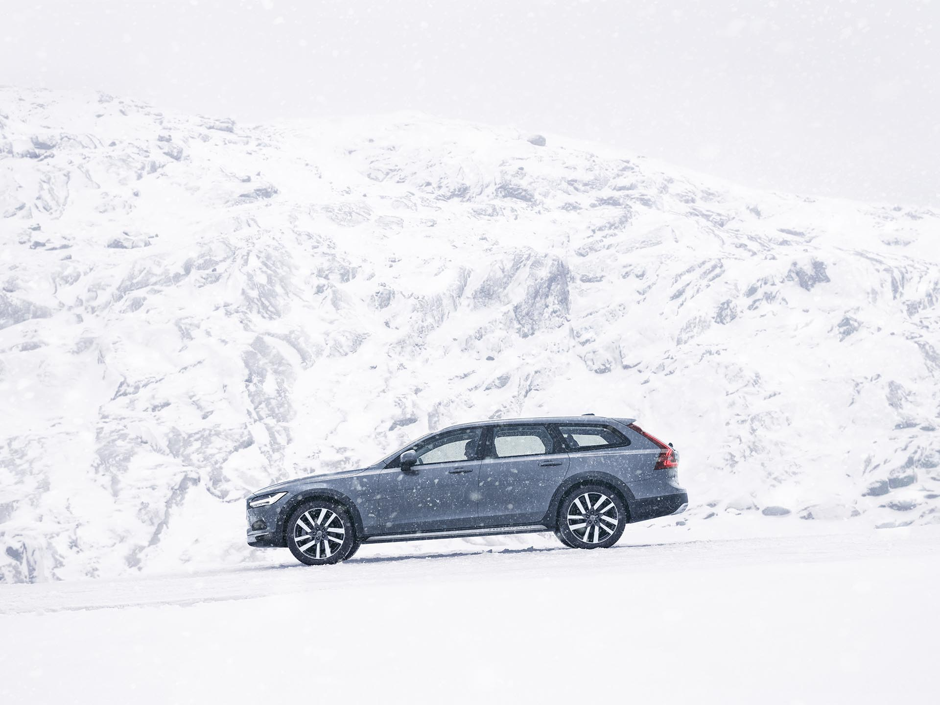 A mussel blue Volvo V90 Cross Country Estate driving in the snowy mountains