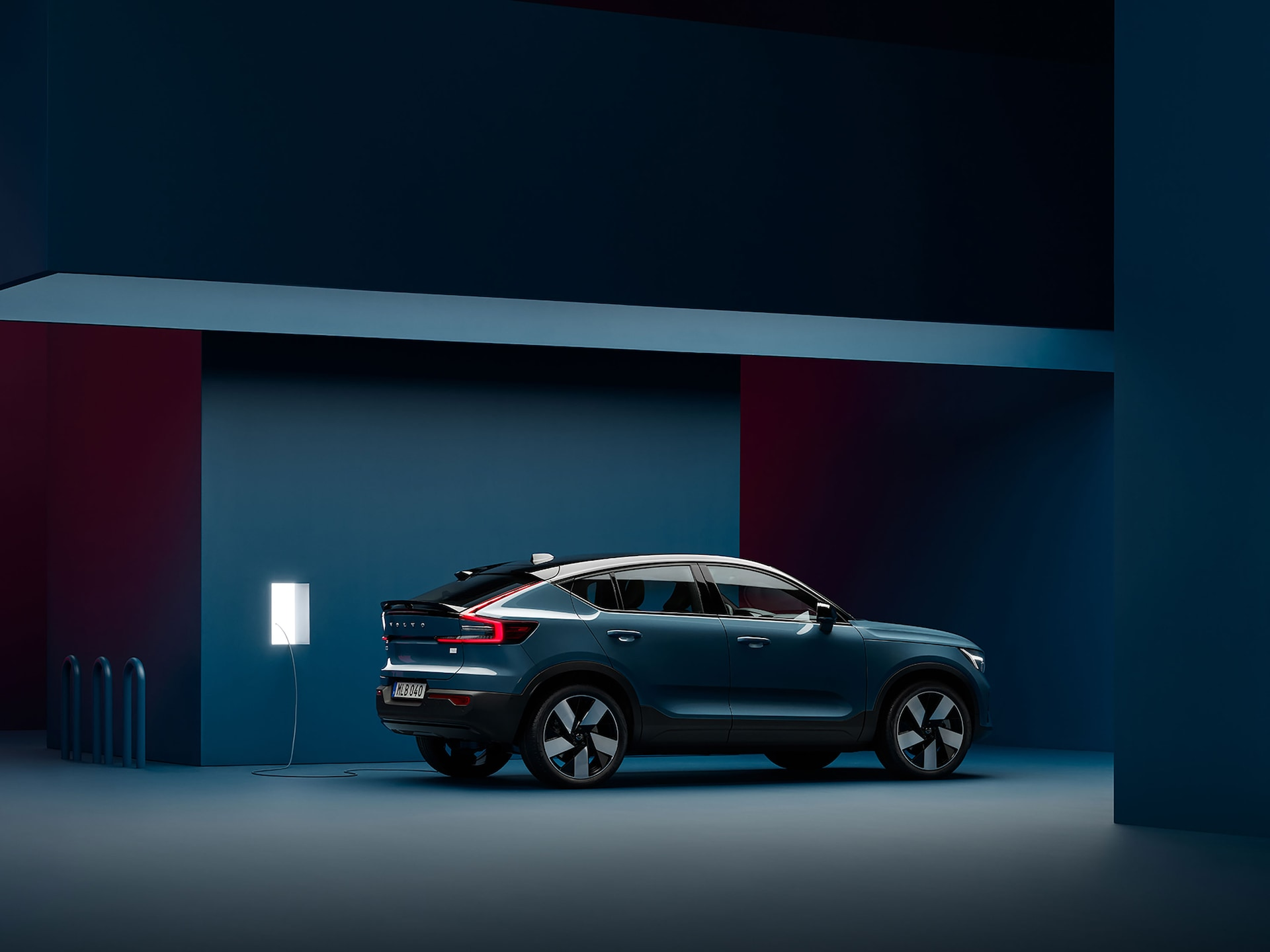A Volvo C40 Recharge is parked in a dark blue room next to a charging station.