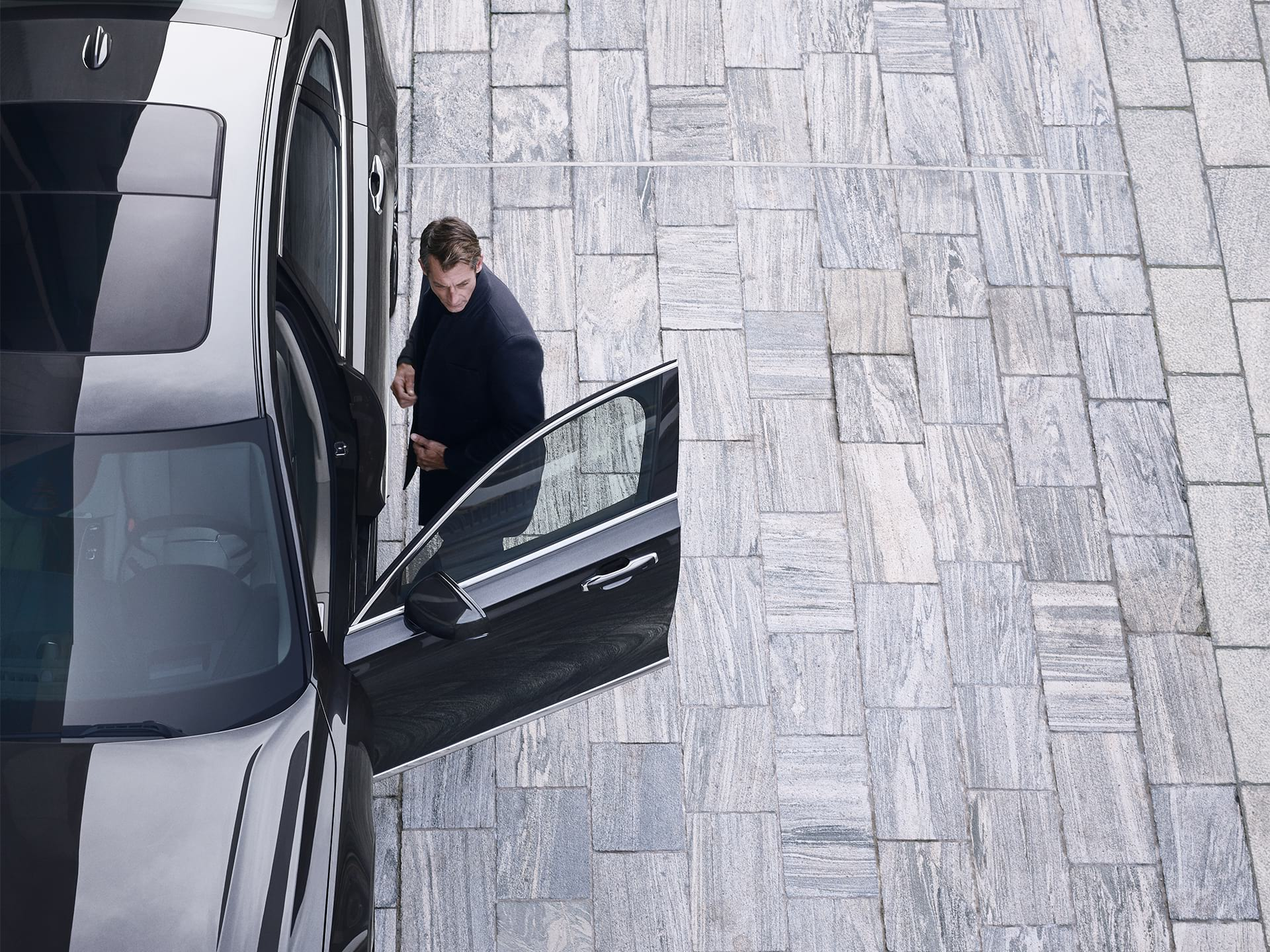 A man is just about to jump into his Volvo S90.