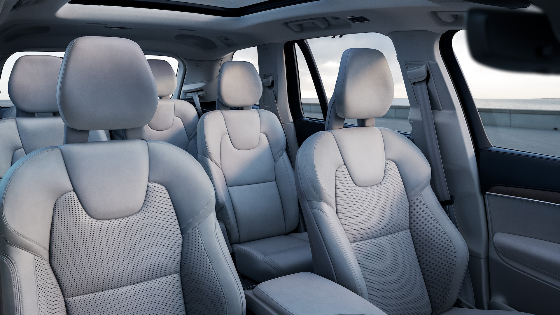 Inside a Volvo XC90 with 3 rows, blonde interior on seats.