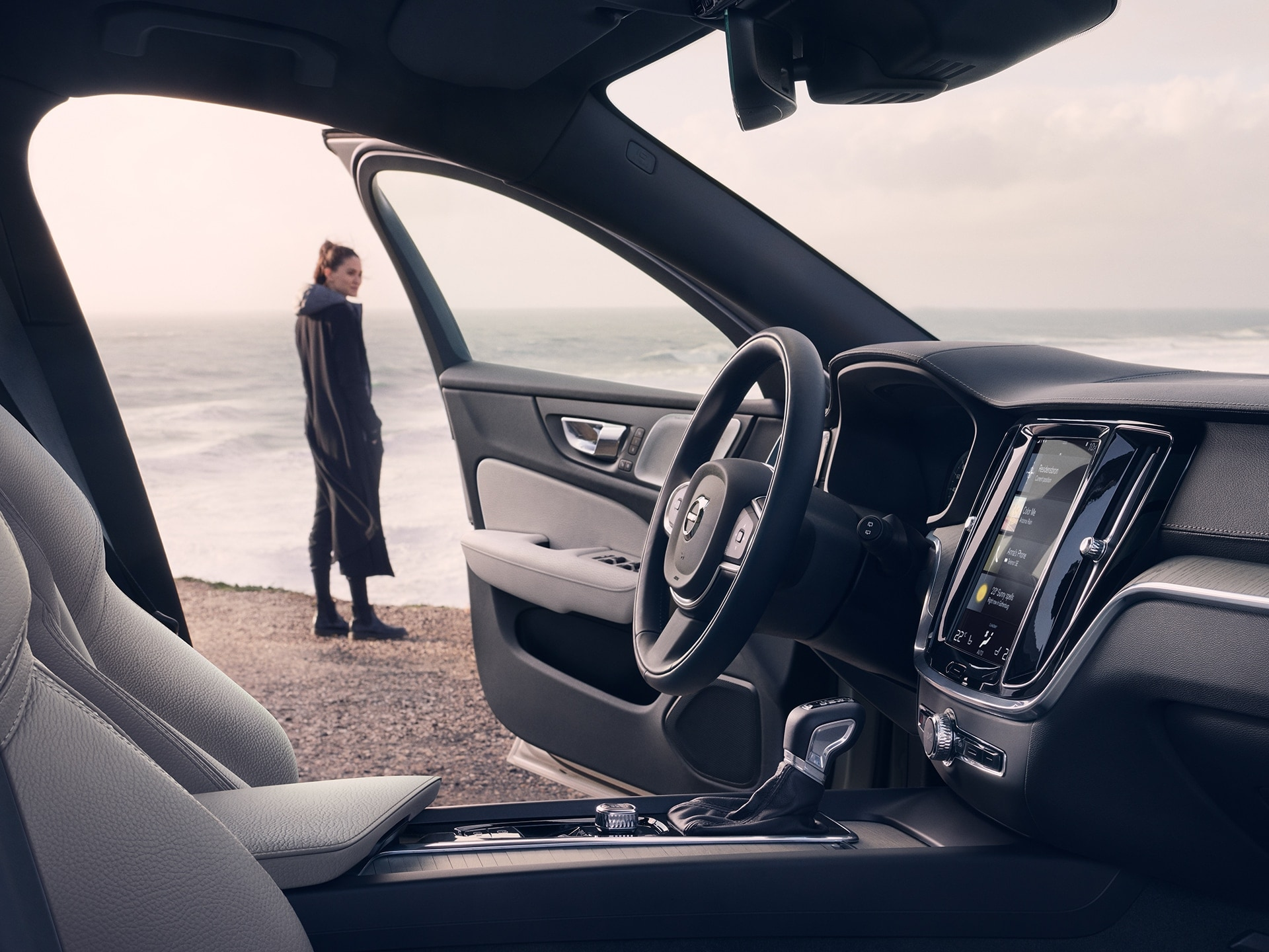 A woman stands along the beach, her V60 Cross Country has one door open
