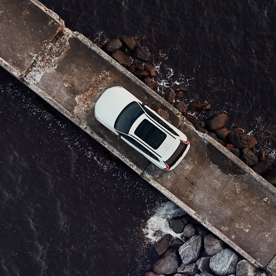 A white Volvo XC60 Recharge is parked on a barge surrounded by the sea